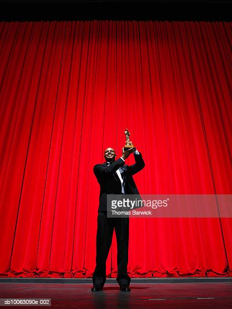 man holding award on stage, smiling - theatrical performance photos et images de collection