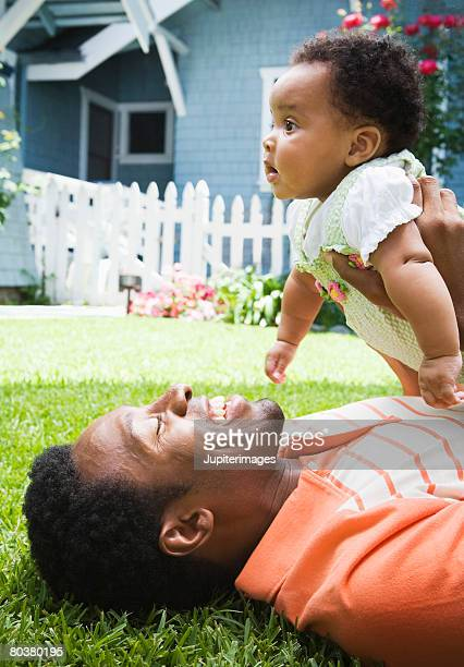 Man holding baby in front of house