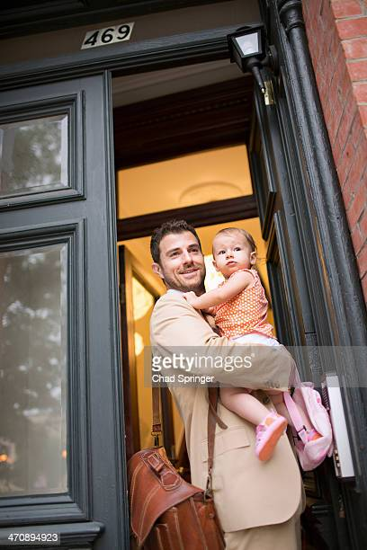 Man holding baby standing at front door