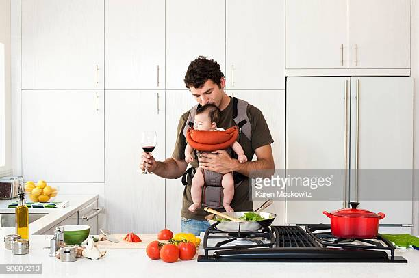 man holding baby while cooking