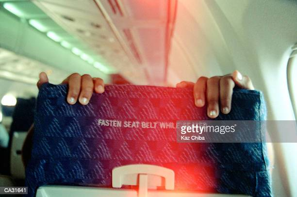Man holding back of aeroplane seat, close-up