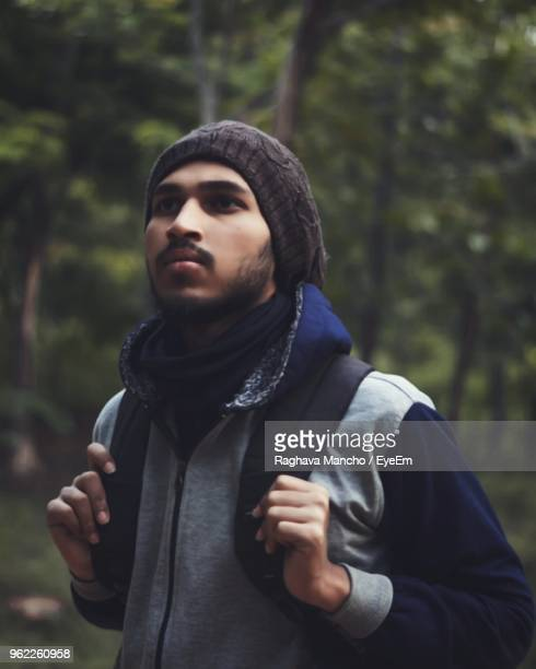 Man Holding Backpack While Standing At Forest