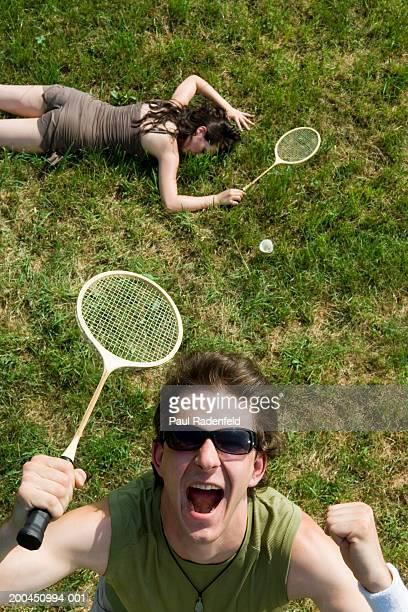 man holding badminton raquet cheering, woman lying on grass, portrait - badminton imagens e fotografias de stock