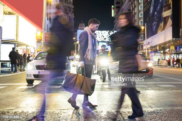 Man holding bag and cell phone crossing a street at night