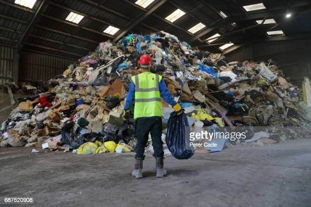 man holding bag of rubbish at rubbish tip - rubbish stock pictures, royalty-free photos & images