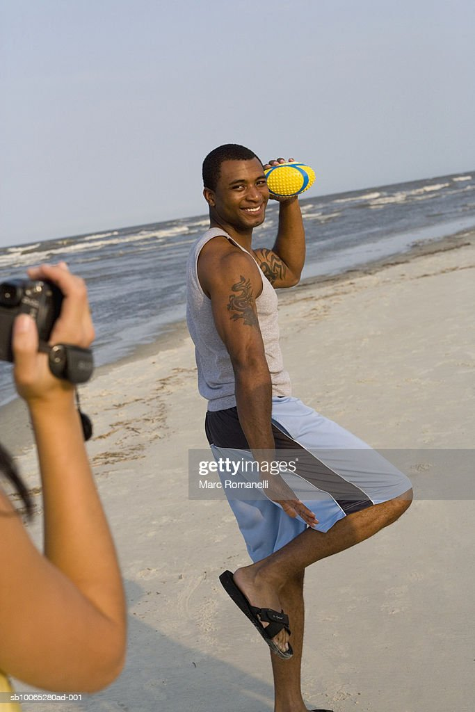 Man holding ball being videotaped on beach : Foto stock