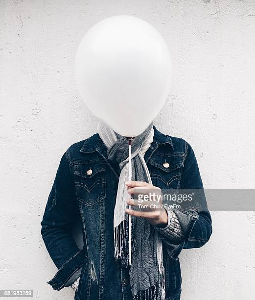 Man Holding Balloon In Front Of His Face