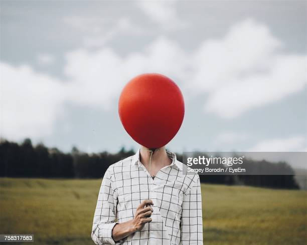 man holding balloon on field against sky - obscured face stock pictures, royalty-free photos & images