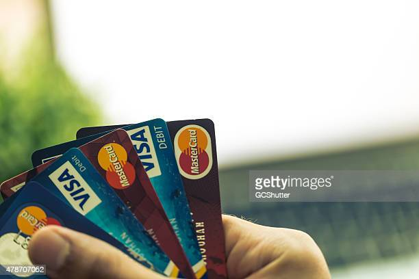 Man holding bank Credit and Debit Cards with computer background
