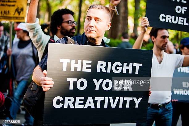 man holding banner in crowd of protestors, new york - may day international workers day stockfoto's en -beelden