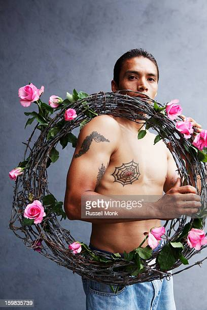 Man holding barbed wire wrapped in roses.