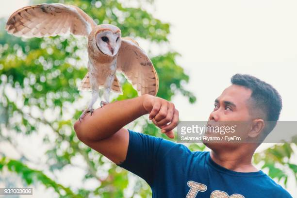 Man Holding Barn Owl At Park