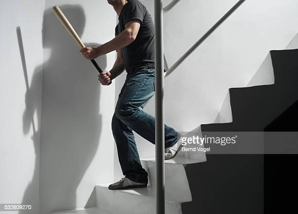 Man Holding Baseball Bat Going Downstairs