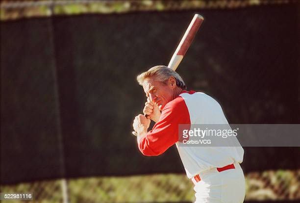 man holding baseball bat - batting stock-fotos und bilder