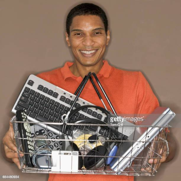 Man Holding Basket of Various Electronics