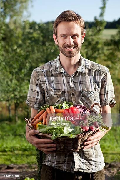 Mann hält Korb mit Gemüse