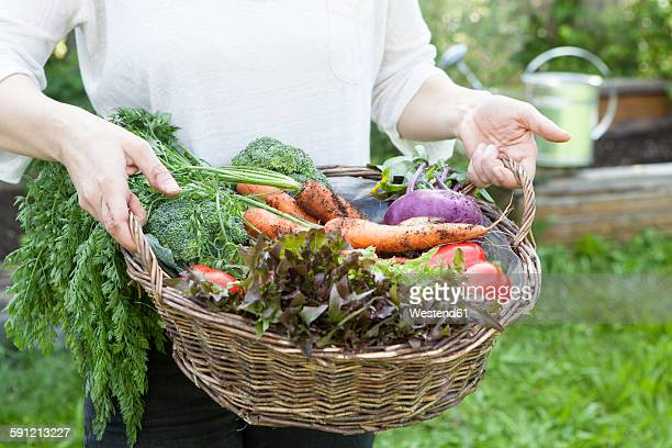 Man holding basket with mixed vegetables