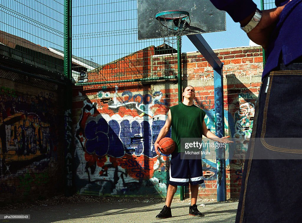 Man holding basketball, arm out, looking at other man : Stockfoto