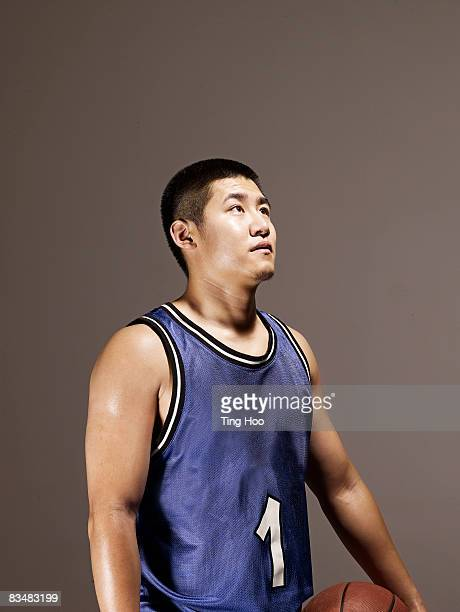 Man holding basketball, looking up