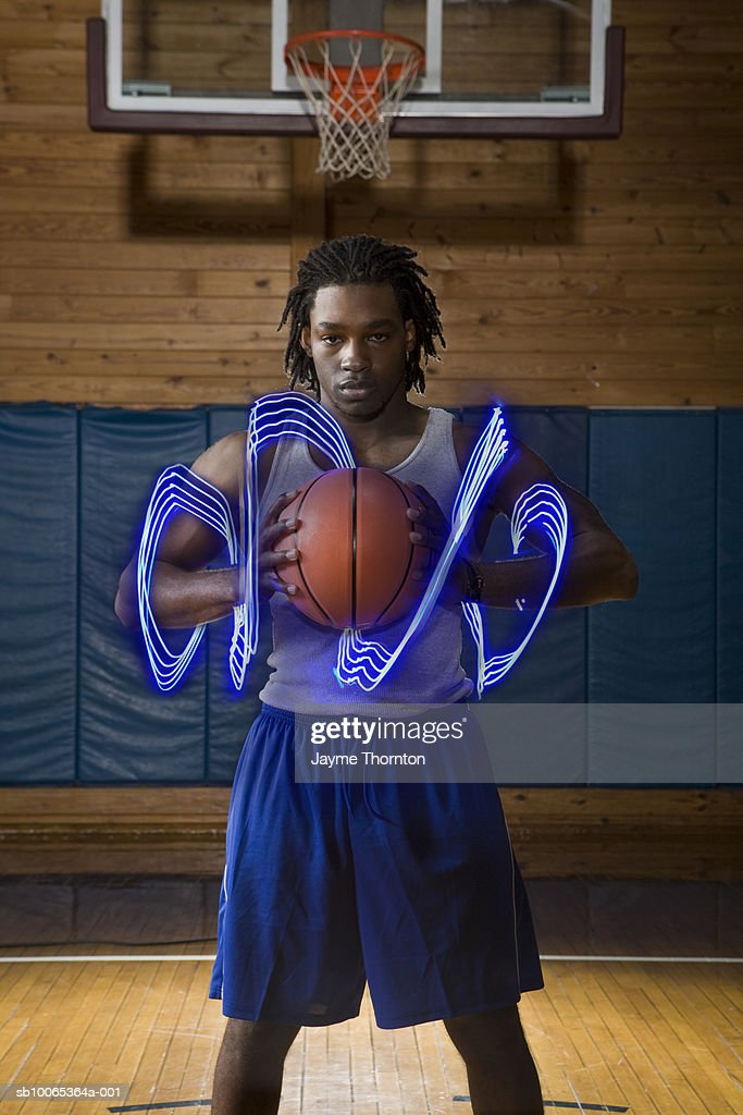 Man holding basketball on indoor court with light trails of movement on arms, portrait (digital composite) : Foto stock