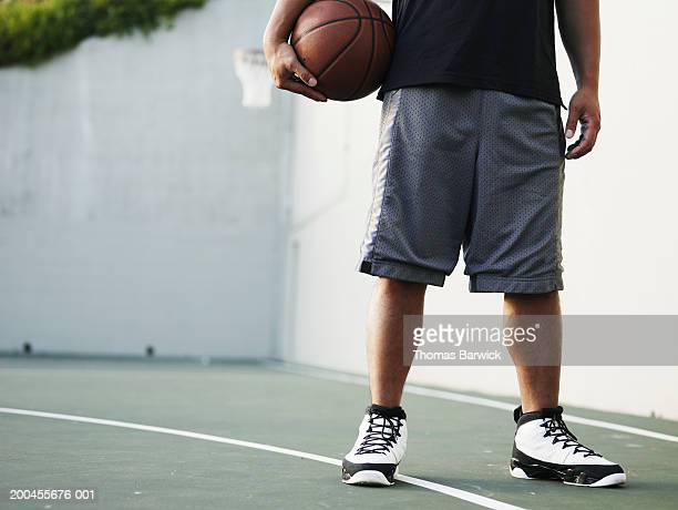 Man holding basketball on outdoor basketball court, low section