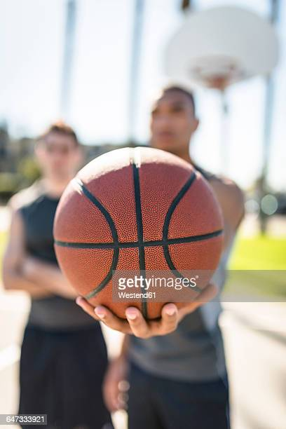 Man holding basketball on outdoor court