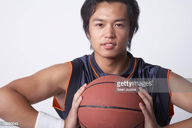 Man holding basketball, portrait