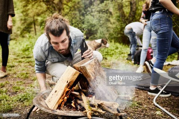 Man holding beer bottle blowing at camp fire