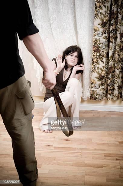 Man Holding Belt Over Woman Cowering on Floor