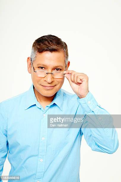 Man holding bifocals looking into camera.