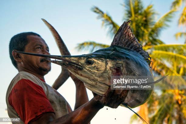 Man Holding Big Fish Against Clear Sky
