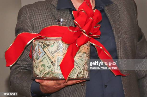 man holding big jar of money - christmas cash stock pictures, royalty-free photos & images