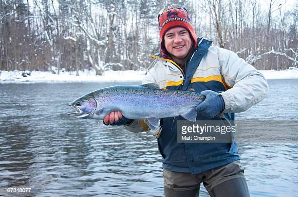 Man Holding Big Steelhead Caught in Winter