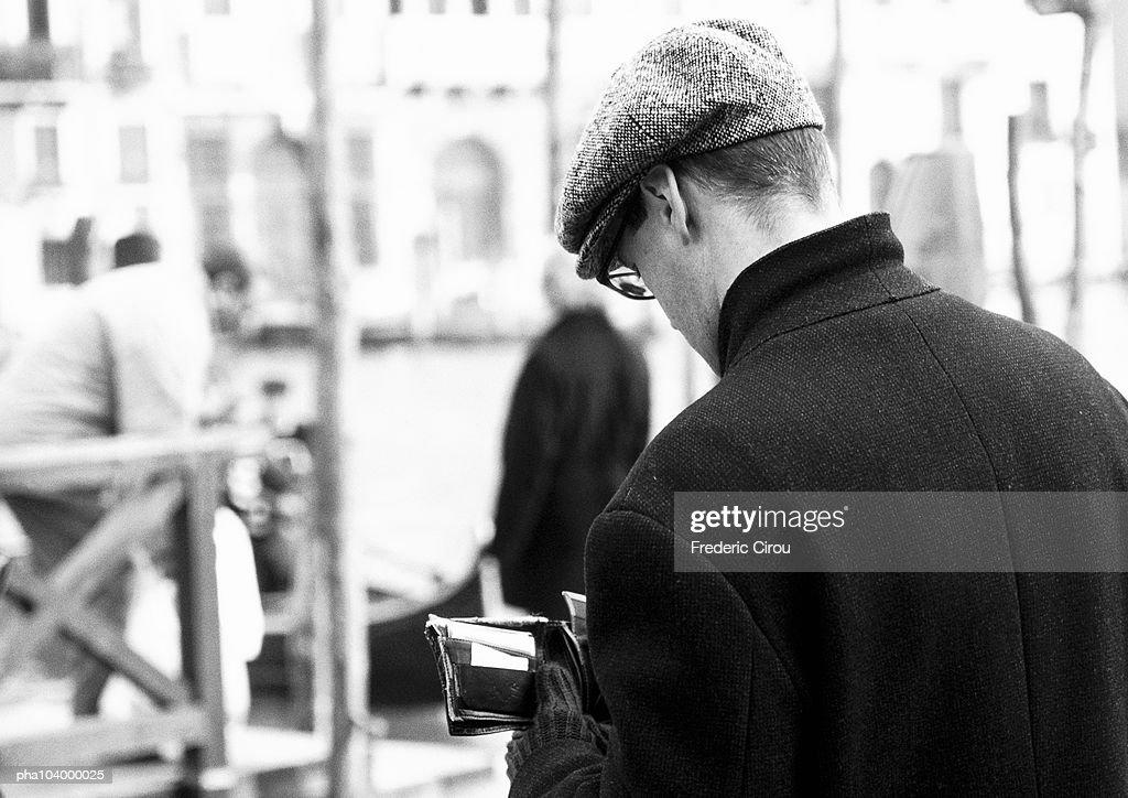 Man holding billfold, rear view, b&w : Stockfoto