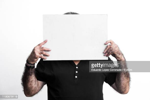 man holding blank paper while standing against white background - obscured face stock pictures, royalty-free photos & images