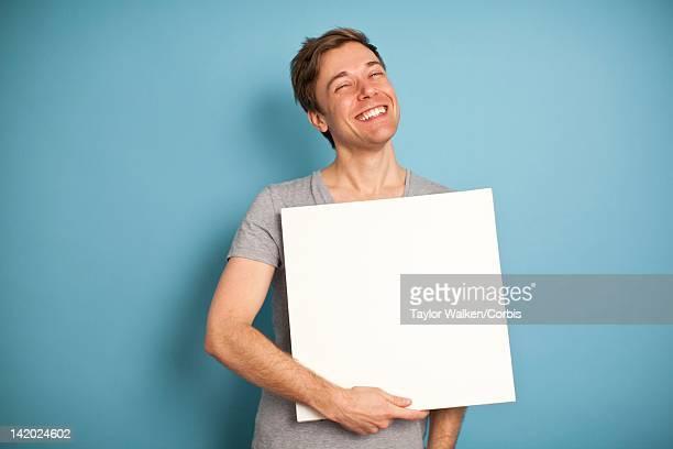 Man holding blank white board