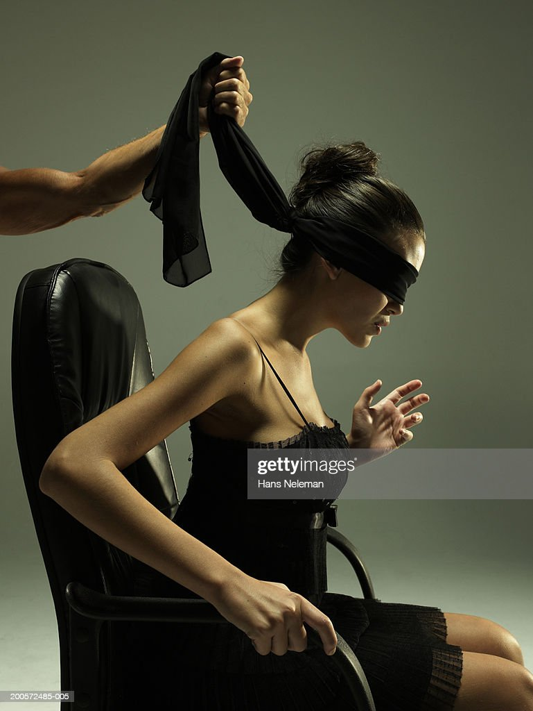 Man Holding Blindfold Over Young Womans Eyes Studio Shot Stock Photo
