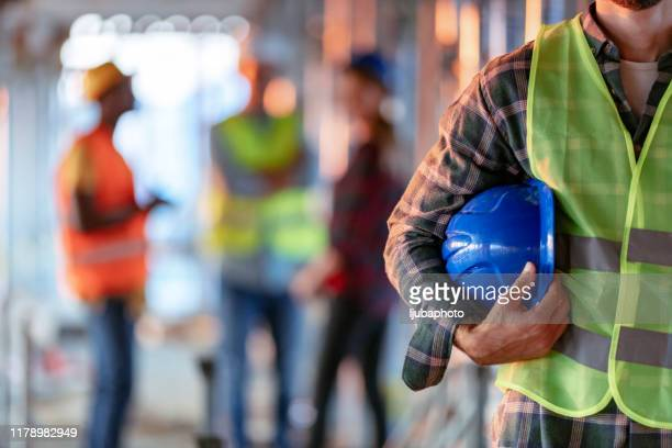 man holding blue helmet close up - sicurezza foto e immagini stock