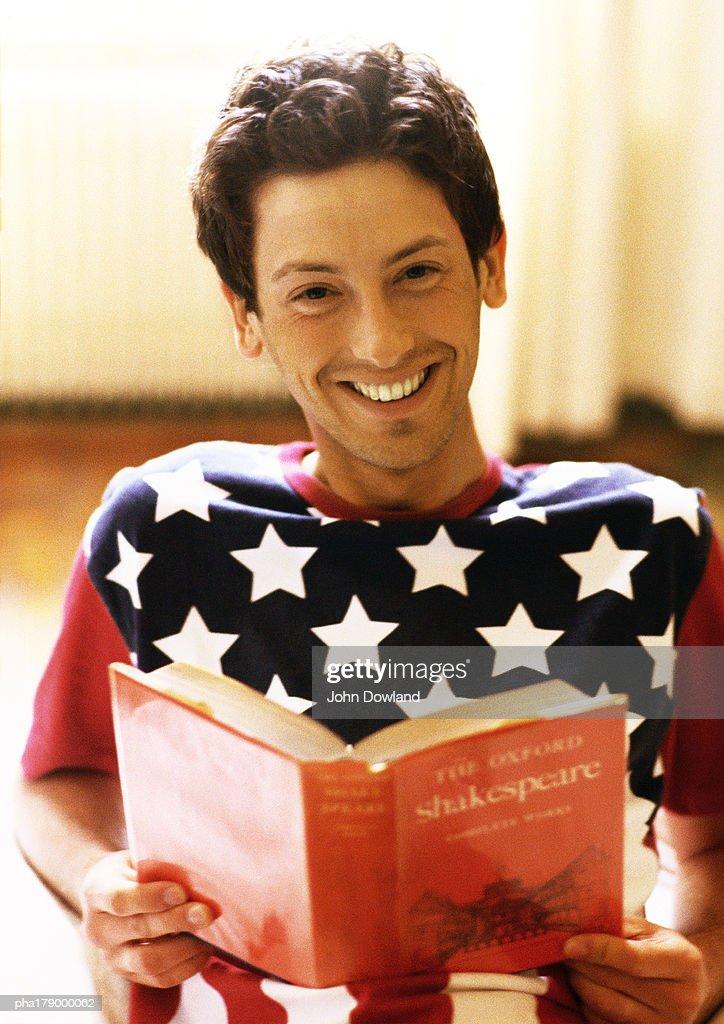 Man holding book, smiling, portrait : Stockfoto