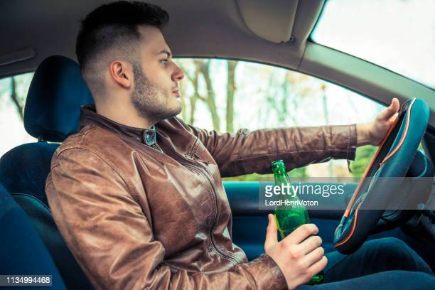 man holding bottle of beer while driving car - drunk driving stock photos and pictures