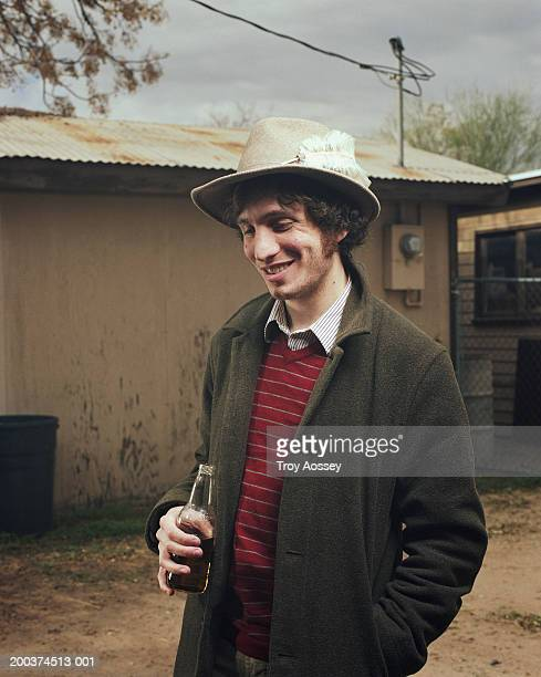 Man holding bottle, smiling