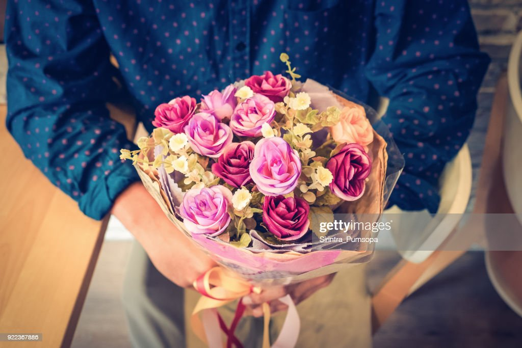 Man holding bouquet of flower. Photo toned style Instagram filters : Stock Photo