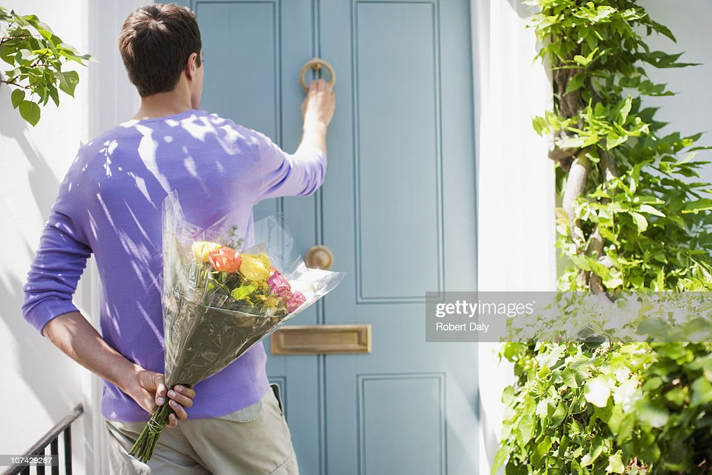 Man holding bouquet of flowers and knocking on door : Stock Photo