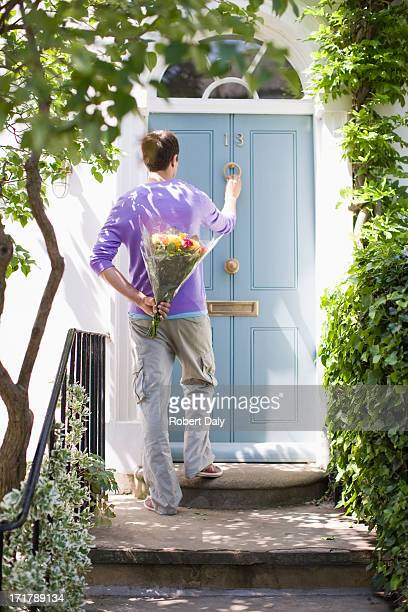 man holding bouquet of flowers and knocking on door - knocking on door stock photos and pictures