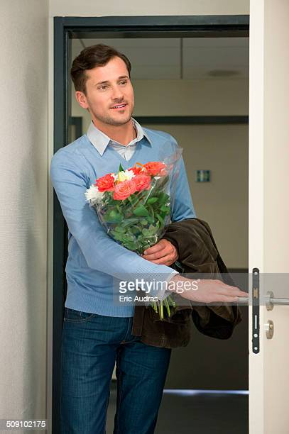 Man holding bouquet of flowers at doorway of hospital