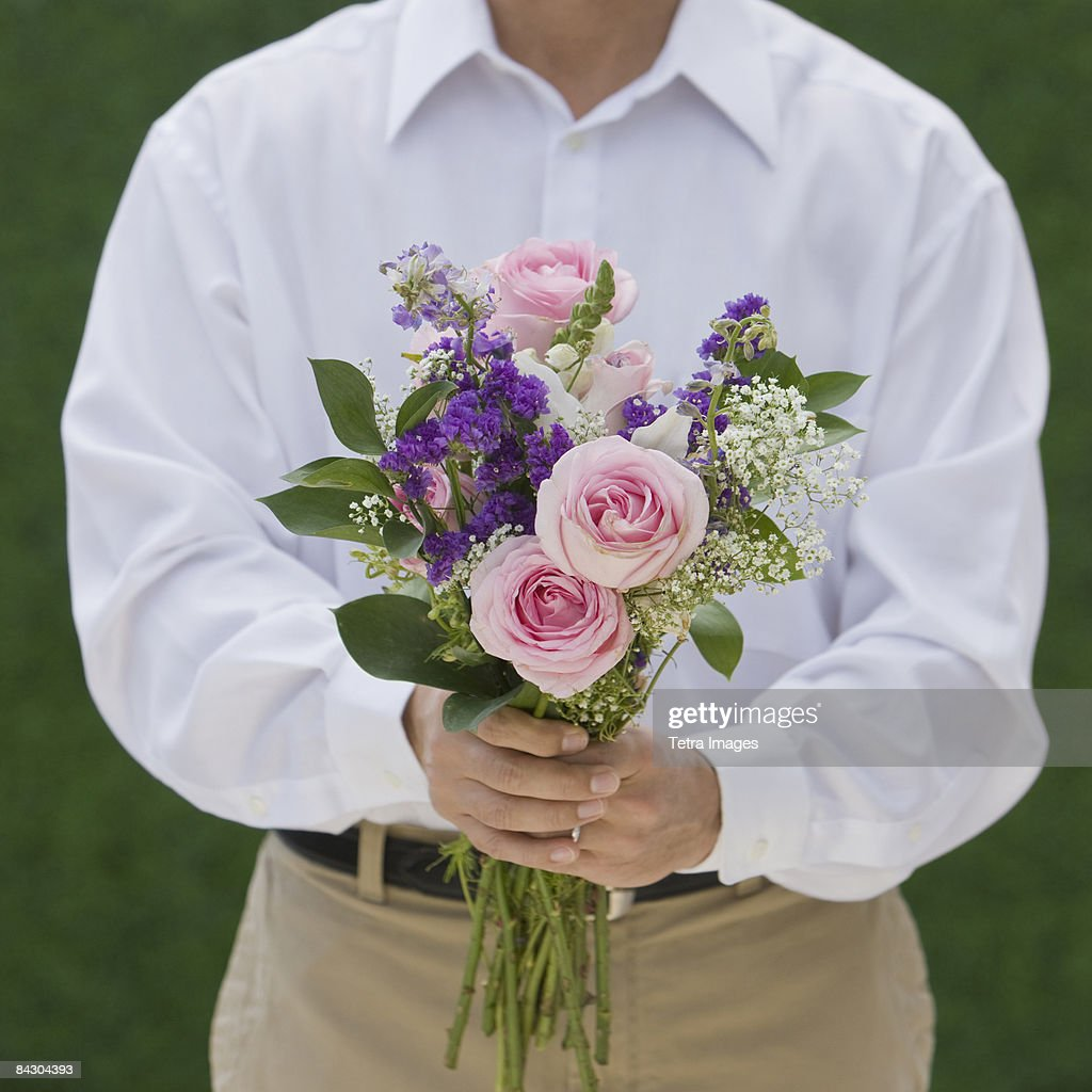 Man holding bouquet of flowers stock photo getty images man holding bouquet of flowers stock photo izmirmasajfo Image collections