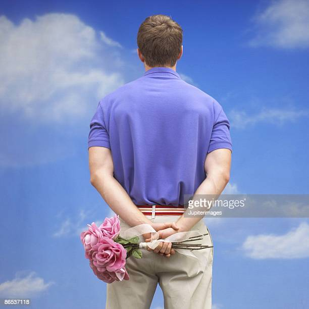 Man holding bouquet of roses behind back