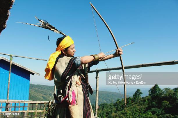 man holding bow and arrow while standing against sky - ko ko htike aung stock pictures, royalty-free photos & images