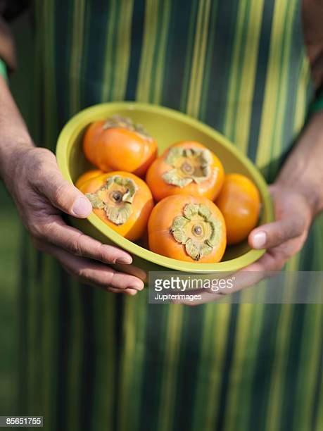 Man holding bowl of persimmons