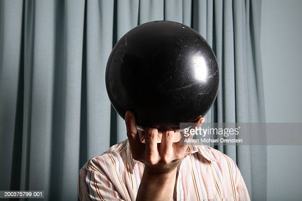 Man holding bowling ball in front of face, close-up